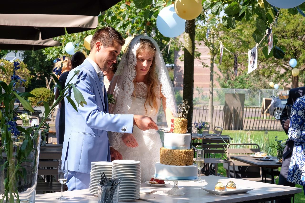 Het aansnijden van de bruidstaart bij Buitensociëteit & Bowling in Deventer